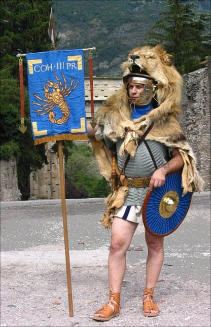A man dressed as an army and carrying a Parma - Parmula